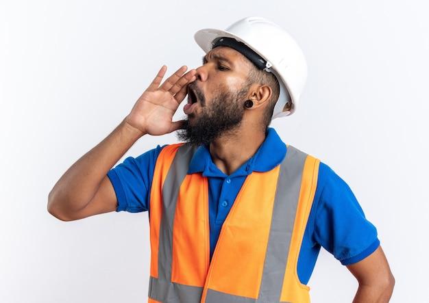 Jeune homme constructeur afro-américain agacé en uniforme avec un casque de sécurité gardant la main près de la bouche appelant quelqu'un regardant de côté isolé sur fond blanc avec espace de copie