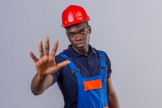 Jeune homme de constructeur afro-américain portant des uniformes de construction et un casque de sécurité debout avec la main ouverte faisant panneau d'arrêt avec un geste de défense d'expression sérieuse et confiante debout