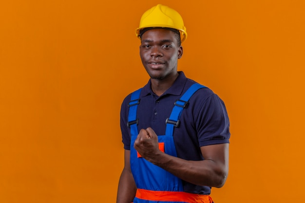 Jeune homme de constructeur afro-américain portant des uniformes de construction et un casque de sécurité montrant le poing souriant debout avec un visage heureux célébrant le concept de gagnant de la victoire sur orange isolé