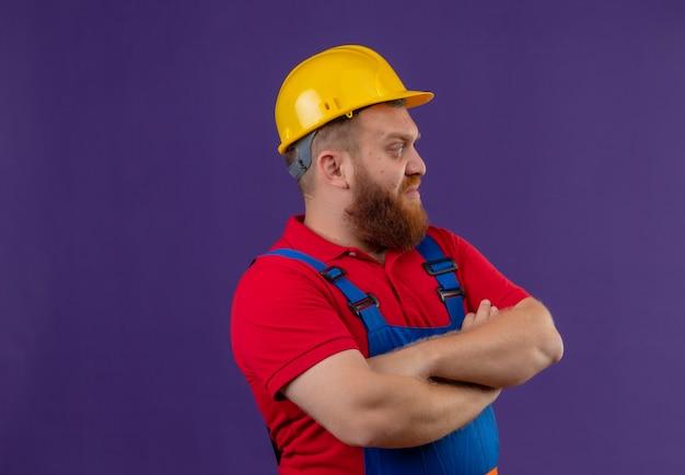 Jeune homme constructeur barbu en uniforme de construction et casque de sécurité avec les bras croisés à côté mécontent sur fond violet