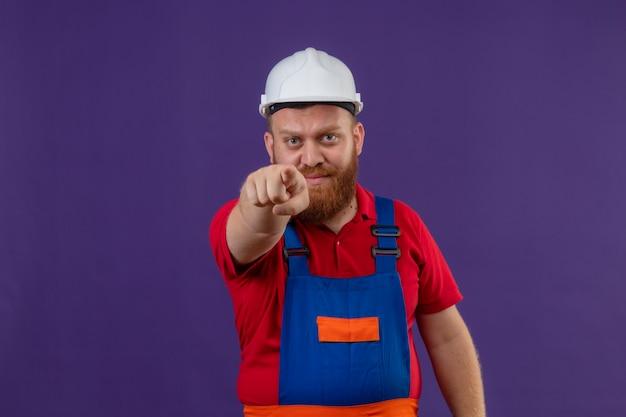 Jeune homme constructeur barbu en uniforme de construction et casque de sécurité pointant vers la caméra mécontent sur fond violet