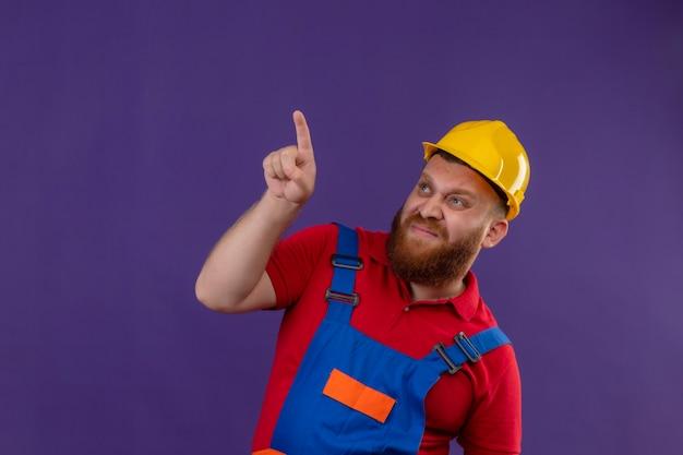 Jeune homme constructeur barbu en uniforme de construction et casque de sécurité à la recherche de quelque chose avec l'index avec une expression dégoûtée sur fond violet