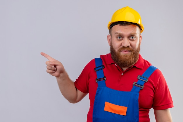 Jeune homme constructeur barbu en uniforme de construction et casque de sécurité regardant la caméra pointant avec le doigt sur le côté avec un visage sérieux