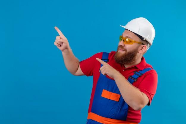 Jeune homme de constructeur barbu en uniforme de construction et casque de sécurité souriant heureux et positif pointant avec les doigts sur le côté