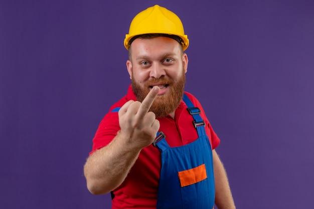 Jeune homme constructeur barbu en uniforme de construction et casque de sécurité souriant joyeusement montrant le majeur sur fond violet