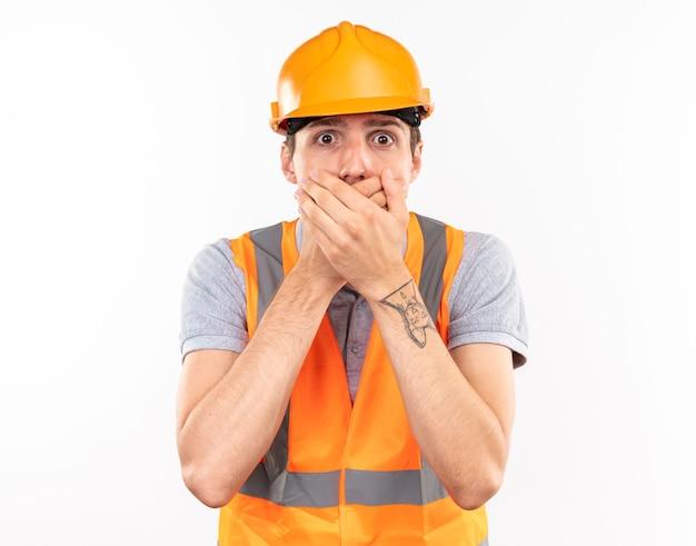 Jeune homme de constructeur effrayé dans la bouche couverte d'uniforme avec des mains