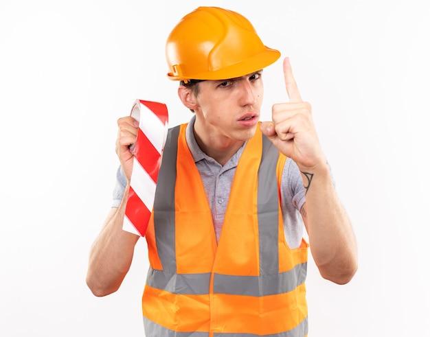 Jeune homme de constructeur strict en uniforme tenant du ruban adhésif montrant un