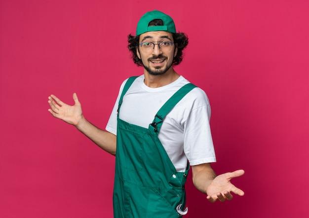 Jeune homme de constructeur surpris en uniforme avec une casquette écartant les mains