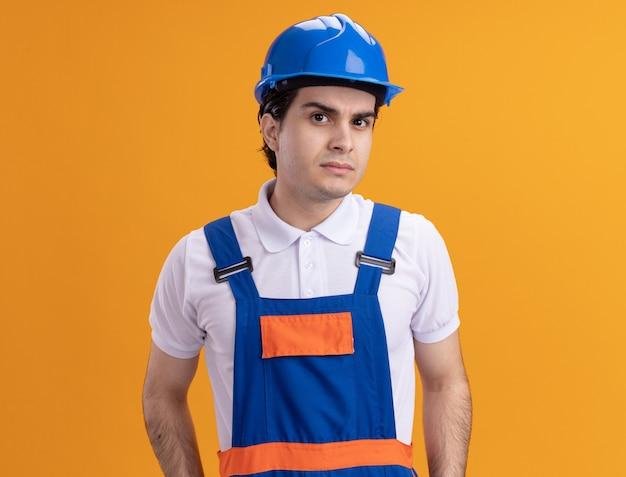 Jeune homme constructeur en uniforme de construction et casque de sécurité à l'avant avec une expression sceptique debout sur un mur orange