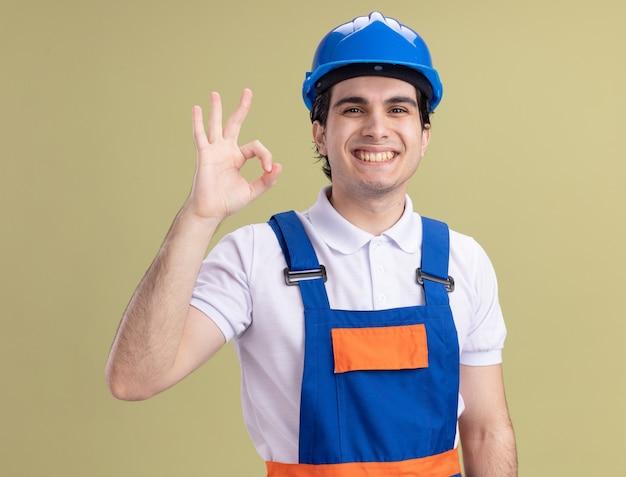 Jeune homme constructeur en uniforme de construction et casque de sécurité à l'avant souriant montrant signe ok debout sur mur vert