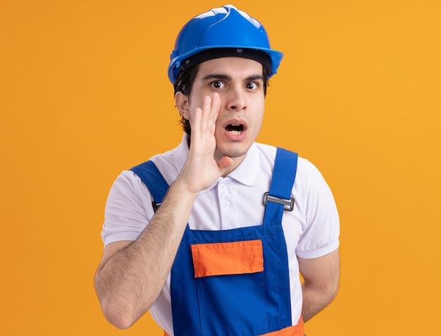 Jeune homme constructeur en uniforme de construction et casque de sécurité chuchotant un secret avec la main ner bouche debout sur le mur orange