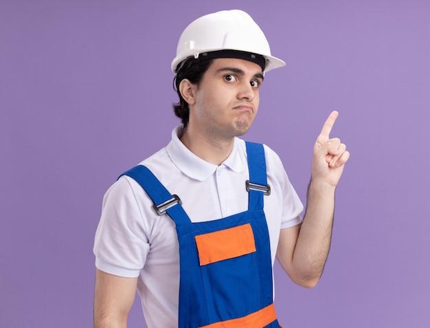 Jeune homme constructeur en uniforme de construction et casque de sécurité à la confusion pointant avec l'index sur le côté debout sur le mur violet