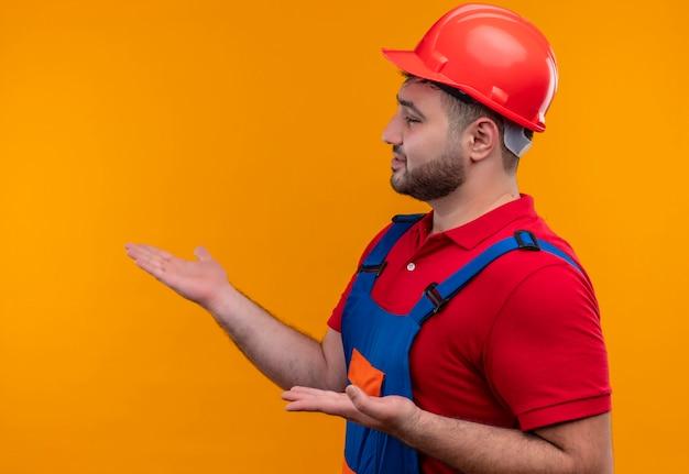 Jeune homme constructeur en uniforme de construction et casque de sécurité à côté présentant avec bras oh mains