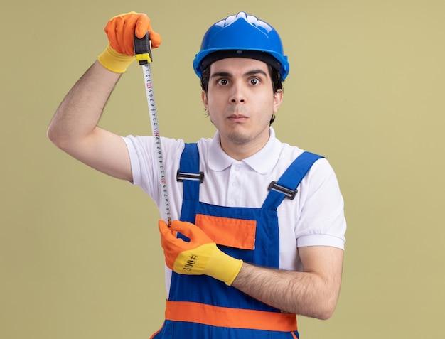 Jeune homme constructeur en uniforme de construction et casque de sécurité dans des gants en caoutchouc tenant un ruban à mesurer à l'avant confus debout sur un mur vert