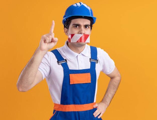 Jeune homme constructeur en uniforme de construction et casque de sécurité avec du ruban adhésif enroulé autour de la bouche à l'avant inquiet pointant avec l'index debout sur le mur orange