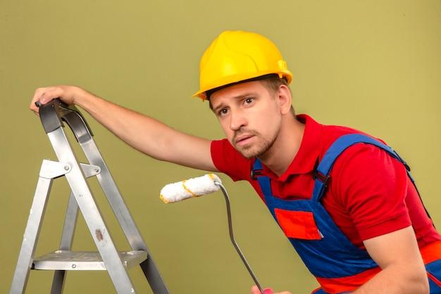 Jeune homme constructeur en uniforme de construction et casque de sécurité sur échelle métallique tenant le rouleau de peinture à la recherche de côté sur mur vert isolé