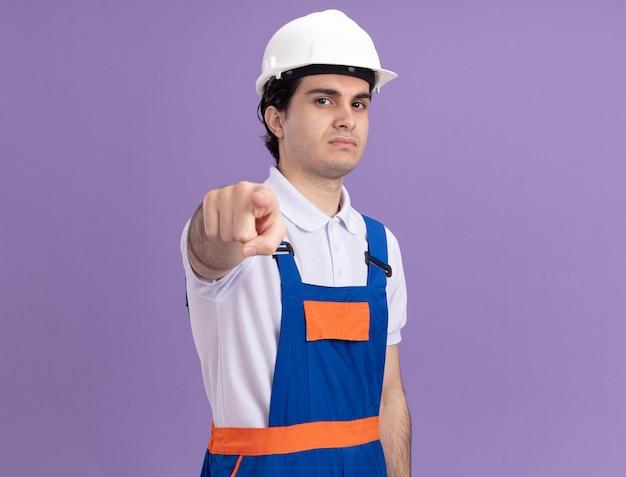 Jeune homme constructeur en uniforme de construction et casque de sécurité pointant avec l'index à l'avant à mécontent de se tenir debout sur le mur violet