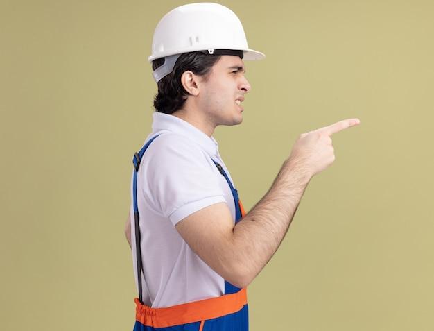 Jeune homme constructeur en uniforme de construction et casque de sécurité pointant avec l'index sur le côté étant confus debout sur le côté sur le mur vert