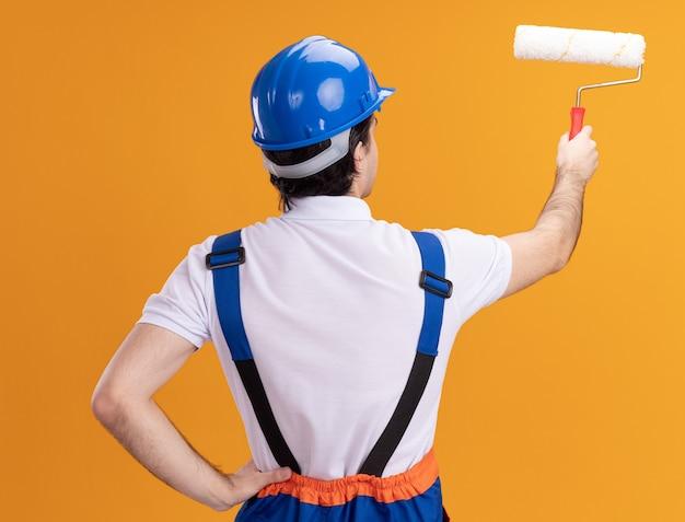Jeune homme constructeur en uniforme de construction et casque de sécurité tenant un rouleau à peinture debout avec son dos sur un mur orange