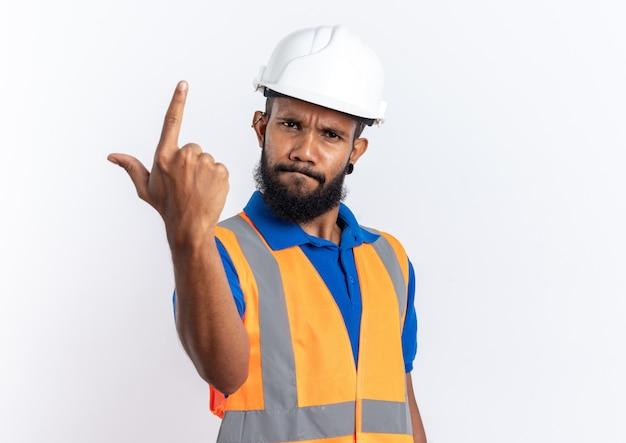 Jeune homme de construction afro-américain agacé en uniforme avec un casque de sécurité pointant vers le haut isolé sur un mur blanc avec espace de copie