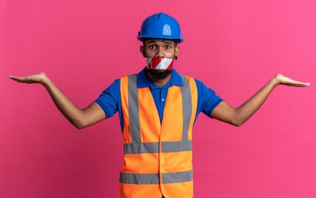 Jeune homme de construction afro-américain anxieux en uniforme avec la bouche d'un casque de sécurité scellée avec du ruban d'avertissement en gardant les mains ouvertes isolées sur fond rose avec espace de copie