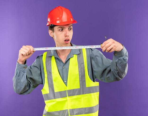 Jeune homme de construction concerné en uniforme s'étendant sur un ruban à mesurer isolé sur un mur bleu