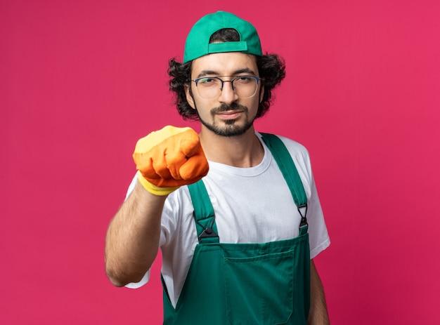Jeune homme de construction confiant portant un uniforme avec une casquette et des gants pointe à l'avant