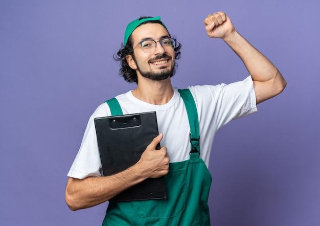 Jeune homme de construction excité portant un uniforme avec une casquette tenant un presse-papiers montrant un geste oui