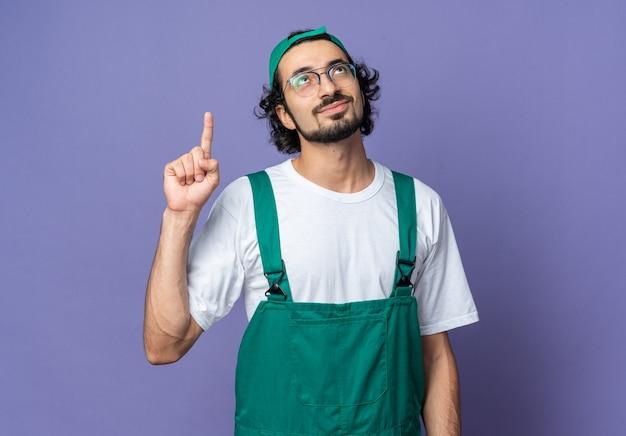 Jeune homme de construction impressionné portant l'uniforme avec des points de casquette vers le haut