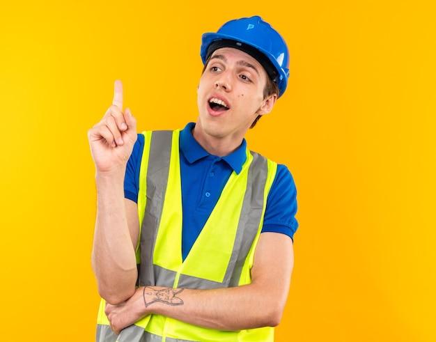 Jeune homme de construction impressionné en uniforme pointe vers le haut