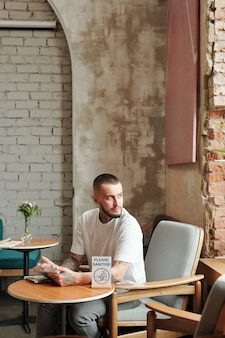 Jeune homme contemplatif avec tablette regardant par la fenêtre alors qu'il était assis dans un petit café de l'hôtel