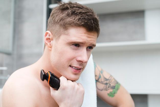 Jeune homme contemplé avec un rasoir électrique à la main à la recherche de suite