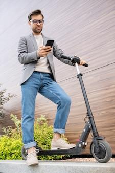 Jeune homme contemporain en smart casualwear lecture message dans smartphone en se tenant debout sur le scooter à l'extérieur