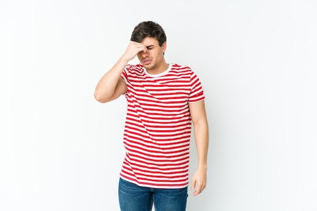 Jeune homme cool ayant mal à la tête, touchant le devant du visage.