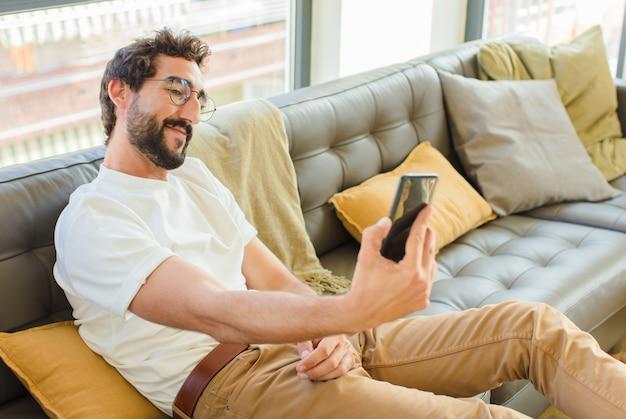 Jeune homme cool barbu assis sur un canapé à la maison