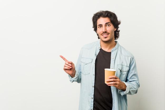 Jeune homme cool, boire un café en souriant et en pointant de côté, montrant quelque chose à l'espace vide.