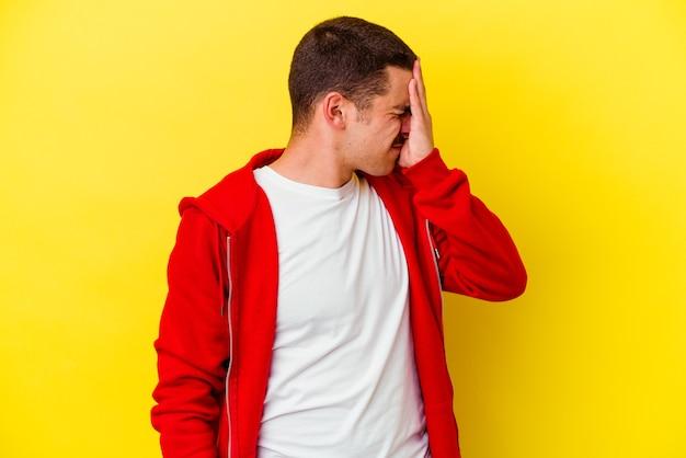 Jeune homme cool caucasien isolé sur jaune ayant mal à la tête, touchant le devant du visage.
