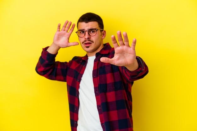 Jeune homme cool caucasien isolé sur mur jaune étant choqué en raison d'un danger imminent