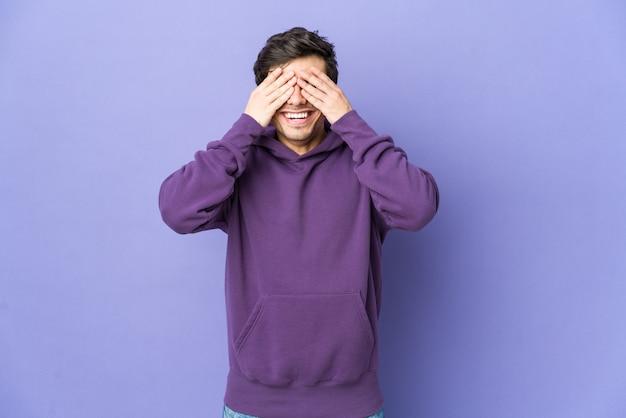 Jeune homme cool couvre les yeux avec les mains, sourit largement en attendant une surprise