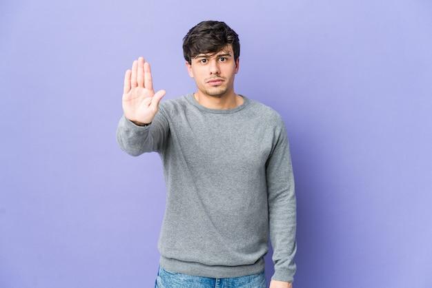 Jeune homme cool debout avec la main tendue montrant le panneau d'arrêt, vous empêchant.