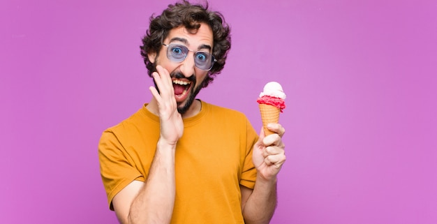 Jeune homme cool fou ayant une glace contre le mur violet