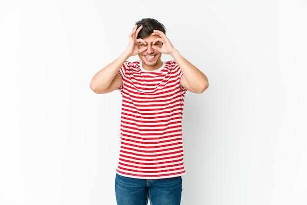 Jeune homme cool montrant un signe correct sur les yeux