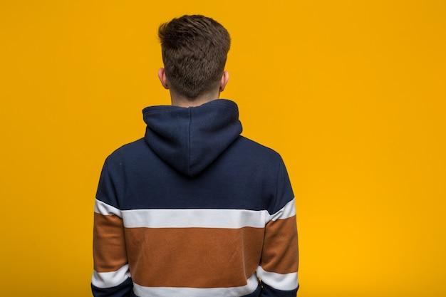 Jeune homme cool portant un sweat à capuche par derrière, regardant en arrière.