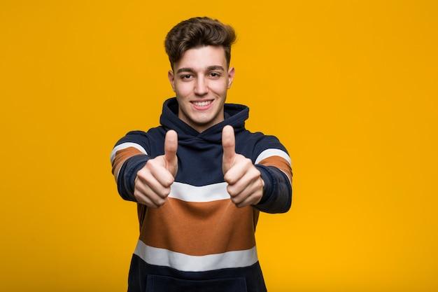 Jeune homme cool portant un sweat à capuche avec les pouces vers le haut, applaudit à quelque chose, soutient et respecte le concept.