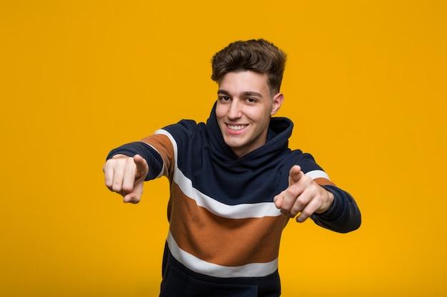 Jeune homme cool portant un sweat à capuche sourires gais pointant vers l'avant.
