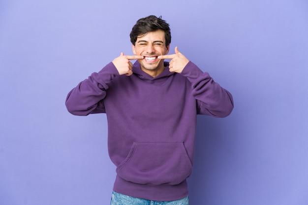 Jeune homme cool sourit, pointant du doigt la bouche.