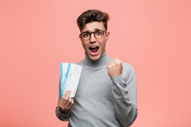 Jeune homme cool tenant un billet d'avion acclamant insouciant et excité. concept de victoire.