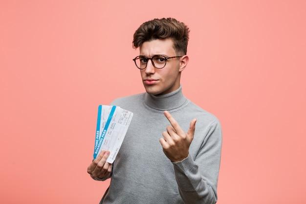 Jeune homme cool tenant un billet d'avion pointé avec le doigt vers vous comme si vous vous rapprochez.