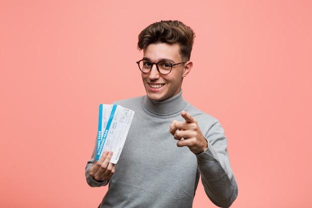 Jeune homme cool tenant un billet d'avion des sourires joyeux pointant vers l'avant.
