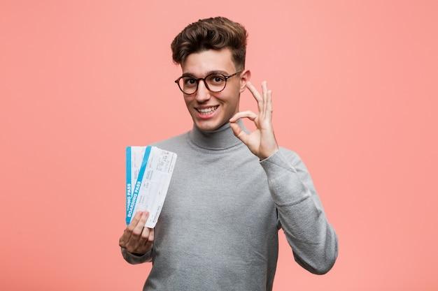 Jeune homme cool tenant un billets d'avion gai et confiant montrant le geste correct.